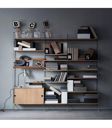 Estantería STRING de 3 módulos con 1 cabinet y 1 revistero en roble con paneles grises.