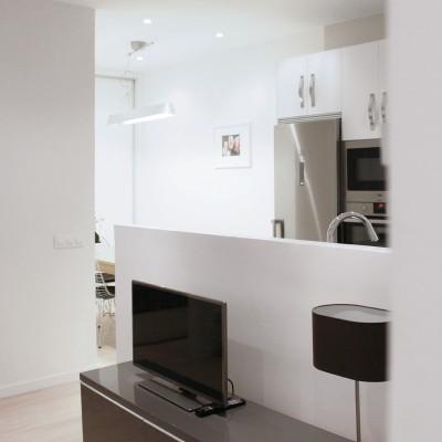 La envolvente neutra y los muebles de cocina blancos ayudan a integrar muy bien la cocina en el estar.