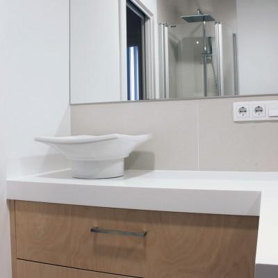 En el baño en suite del dormitorio ganado a la zona de servicio se necesitaba una gran superficie de trabajo. Como las dimensiones del baño eran reducidas, diseñamos un mueble a medida que optimizara el espacio.
