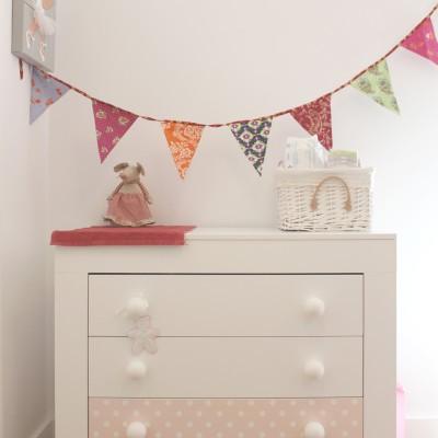 El dormitorio infantil se decoró en tonos rosa con elementos como banderines, lámparas nube, etc.