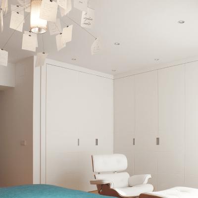 En la zona de vestidor, completa la decoración el Lounge Chair con Ottoman de los Eames en blanco.