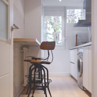 Para la cocina se propuso una distribución del amueblamiento más funcional y se rescató parte de una ventana tapada anteriormente por muebles. Se incorporó así mismo una pequeña barra de madera para los desayunos.