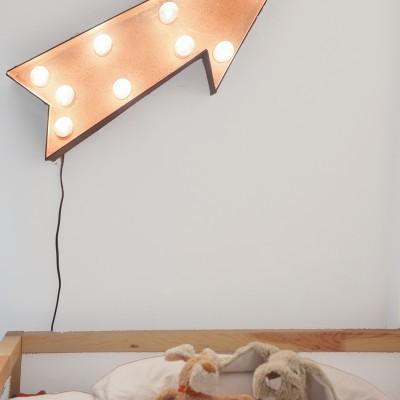 La luz en forma de flecha sobre la cama da un toque divertido y ayuda a dar estilo y luminosidad.