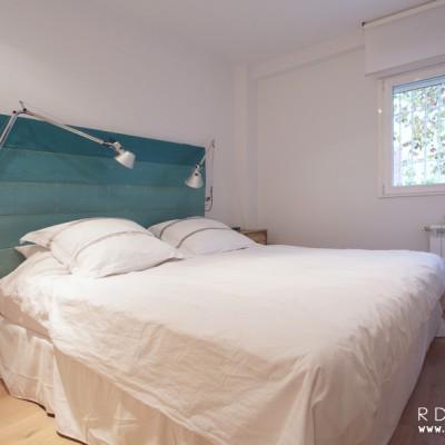 En el dormitorio principal, la propietaria quería instalar un cuadro con tonos azules al que tenía un cariño especial. Por eso propusimos un cabecero en los mismos tonos que otorgase un estética homogénea a la estancia.