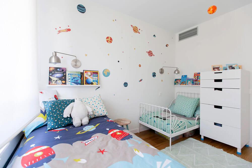 Proyecto de R de Room Amazing Homes. Dormitorio infantil con cama nido y cama extensible blancas y decoración inspirada en el universo.
