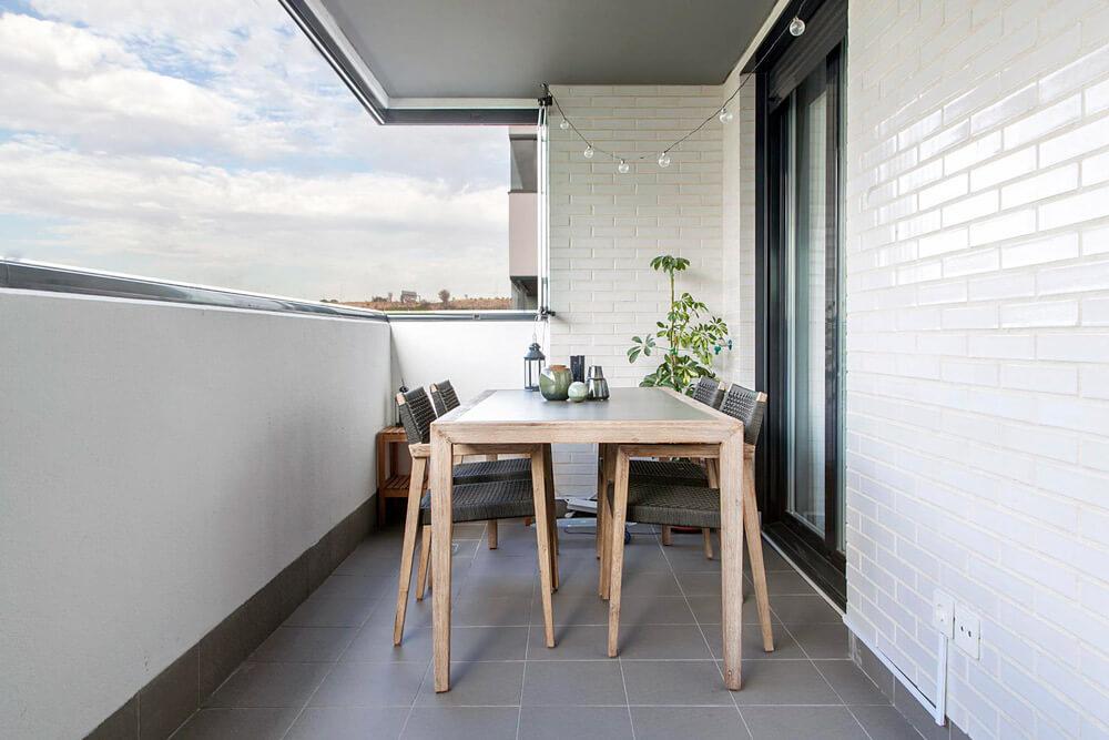 Proyecto de R de Room Amazing Homes. Terraza con mesa de comedor y sillas de madera maciza de acacia. Decoración de centro de mesa con jarrones de la firma danesa Bloomingville.