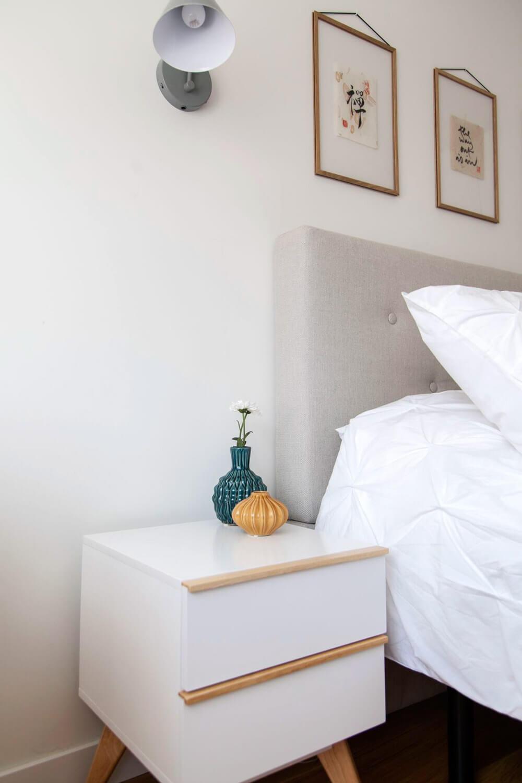 Proyecto de R de Room Amazing Homes. Dormitorio principal de diseño nórdico con cabecero tapizado en gris, mesillas de noche blancas.