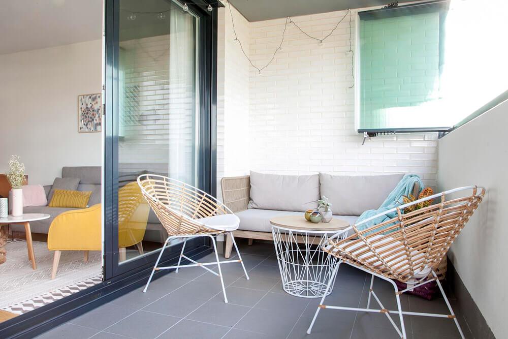 Proyecto de R de Room Amazing Homes. Terraza con sofá de madera maciza de acacia y cojines tapizados en gris y butacas de ratán y metal lacado en blanco.
