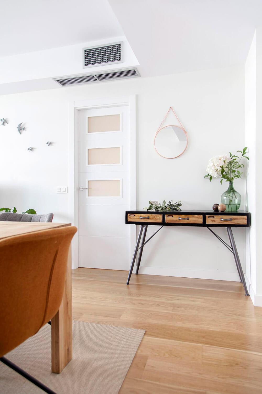 Proyecto de R de Room Amazing Homes. Conjunto de consola URBAN y espejo BOLINA en cobre de House Doctor. Decoración con damajuana y bolas decorativas de Bloomingville.