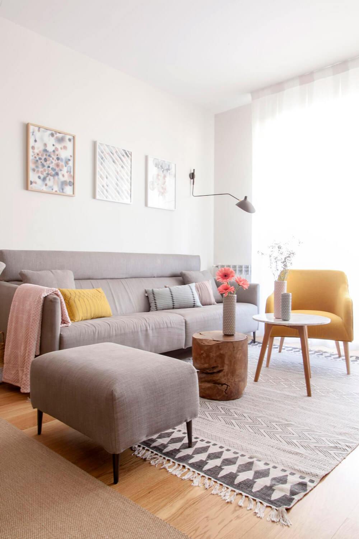 Proyecto de R de Room Amazing Homes. Zona de estar con sofá tapizado en gris con fundas desenfundables, ottoman a juego y butaca tapizada en color mostaza modelo HALL. Las mesas de centro son una combinación de mesa de mármol y tronco de madera de teka. El espacio está delimitado por la alfombra BLOCK de House Doctor.