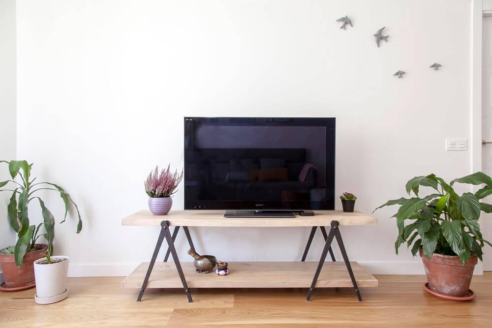Proyecto de R de Room Amazing Homes. Mueble de TV modelo PLATFORM compuesto por dos baldas de madera maciza. Decoración de pared con golondrinas esmaltadas en color gris claro.