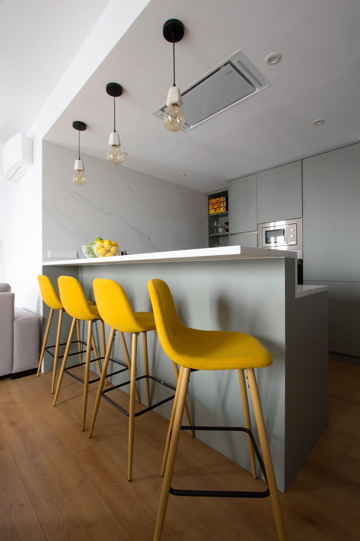 """RdeRoom-MADERA reforma e interiorismo de vivienda para alquiler de lujo en Malasaña. Cocina integrada """"open concept"""". Detalle de la barra con taburetes tapizados."""