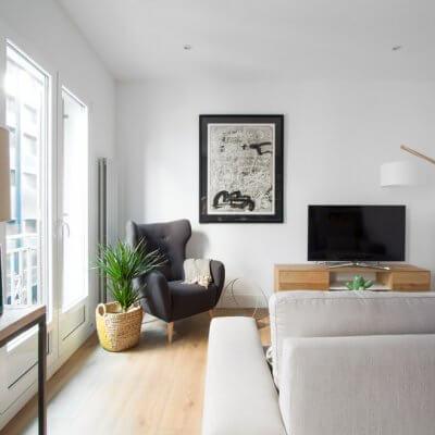 RdeRoom-MADERA reforma e interiorismo de vivienda para alquiler de lujo en Malasaña. Estar con orejero, sofá gris y mueble TV madera