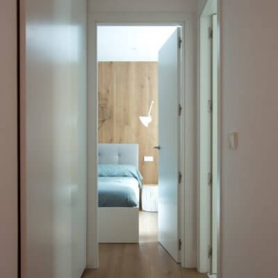 RdeRoom-MADERA reforma e interiorismo de vivienda para alquiler de lujo en Malasaña. vista del dormitorio desde el pasillo.