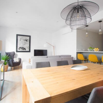 RdeRoom-MADERA reforma e interiorismo de vivienda para alquiler de lujo en Malasaña. Estar-comedor con cocina integrada. Mesa de madera. Taburetes tapizados.