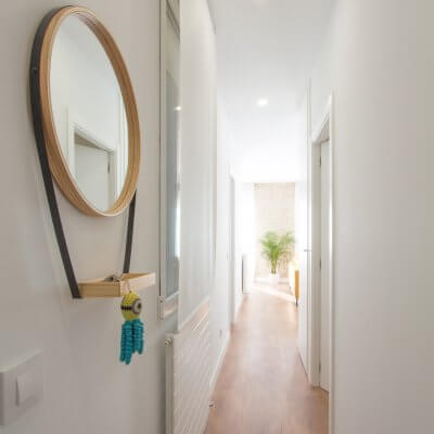 Proyecto de reforma de vivienda en Chamberí II (Madrid) de R de Room. Espejo circular con bandeja para recibidor. Suelo laminado de madera. Radiadores Runtal.