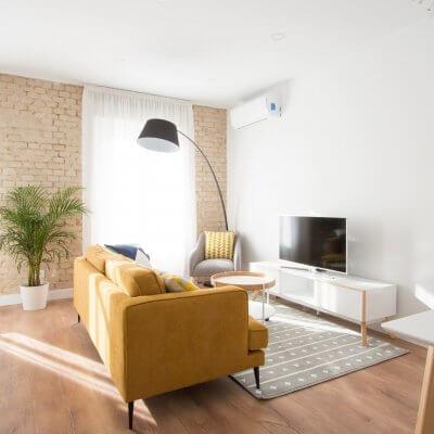 Proyecto de reforma de vivienda en Chamberí II (Madrid) de R de Room. Zona de estar con sofá modelo MAD en color mostaza de estilo mid-century, mueble de tv y mesa de centro con ruedas de estilo escandinavo. Butaca gris y lámpara de pie arco en color negro. Pared de ladrillo visto original.