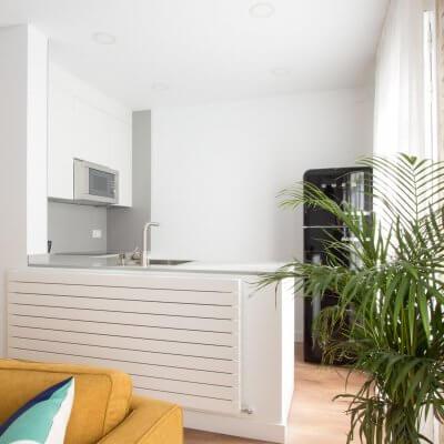 Proyecto de reforma de vivienda en Chamberí II (Madrid) de R de Room. Cocina abierta con península y frigorífico SMEG. Pared de ladrillo visto original. Radiador Runtal.
