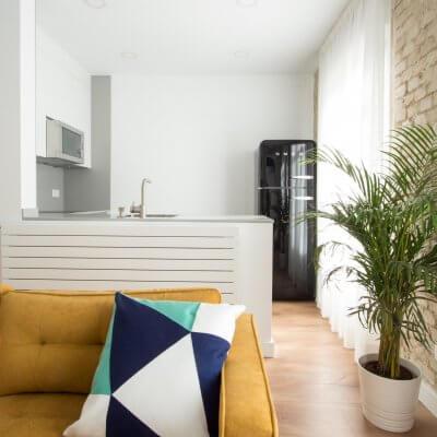 Proyecto de reforma de vivienda en Chamberí II (Madrid) de R de Room. Cocina abierta con península y frigorífico SMEG en color negro. Sofá modelo MAD en color mostaza de estilo mid-century. Pared de ladrillo visto original. Radiador Runtal.