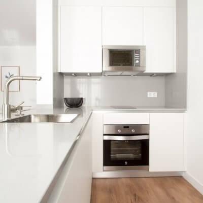 Proyecto de reforma de vivienda en Chamberí II (Madrid) de R de Room. Cocina abierta con península. Muebles blancos y encimera de Silestone en color gris claro.