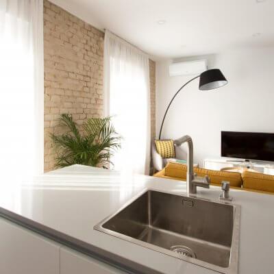 Proyecto de reforma de vivienda en Chamberí II (Madrid) de R de Room. Cocina abierta con península. Sofá modelo MAD en color mostaza de estilo mid-century. Lámpara de pie con forma de arco en color negro.