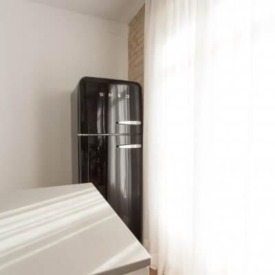 Proyecto de reforma de vivienda en Chamberí II (Madrid) de R de Room. Cocina abierta con península y frigorífico SMEG en color negro. Pared de ladrillo visto original. Radiador Runtal.