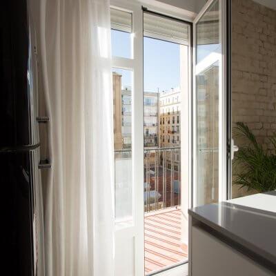 Proyecto de reforma de vivienda en Chamberí II (Madrid) de R de Room. Ventana hacia la terraza desde la cocina. Pared de ladrillo visto original.