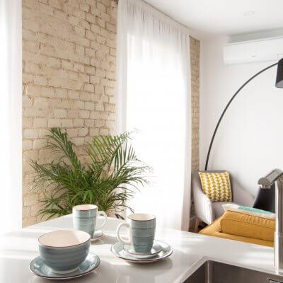 Proyecto de reforma de vivienda en Chamberí II (Madrid) de R de Room. Cocina abierta al salón con península. Muebles blancos y encimera de Silestone en color gris claro. Pared de ladrillo visto original.