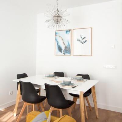 Proyecto de reforma de vivienda en Chamberí II (Madrid) de R de Room. Estar-comedor de estilo escandinavo. Lámpara de techo Sputnik resturada. Láminas de gran formado de Desenio.
