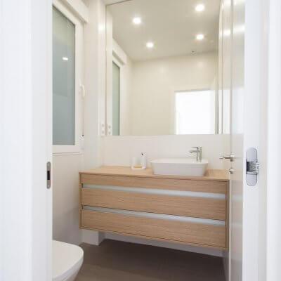 Proyecto de reforma de vivienda en Chamberí II (Madrid) de R de Room. Baño minimalista en balnco y madera. Espejo a medida.