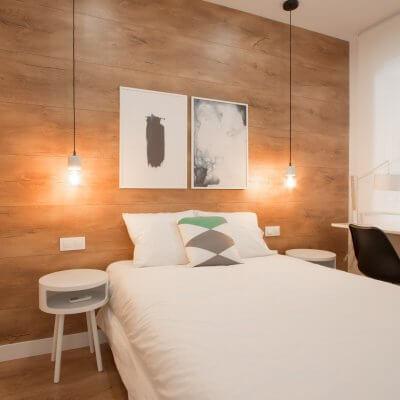 Proyecto de reforma de vivienda en Chamberí II (Madrid) de R de Room. Dormitorio principal con suelo laminado de madera y pared del cabecero forrada en laminado de madera. Lámparas colgantes de mármol blanco bombilla Edison. Mesita de noche modelo BLOCK en color blanco. Zona de escritorio.