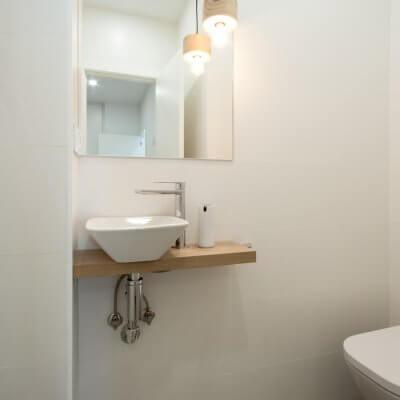 Proyecto de reforma de vivienda en Chamberí II (Madrid) de R de Room. Aseo con lámpara de techo colgante. Casquillo de madera con bombilla EDISON. Encimera a medida con lavabo sobre encimera de dimensiones reducidas.