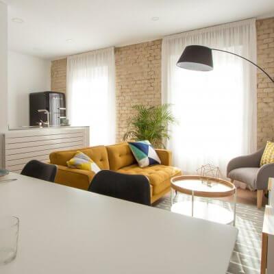 Proyecto de reforma de vivienda en Chamberí II (Madrid) de R de Room. Estar-comedor de estilo escandinavo. Lámpara de techo Sputnik resturada. Sofá modelo MAD en color mostaza y muebles de diseño nórdico en blanco y madera. Láminas de gran formado de Desenio.