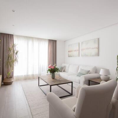 En la zona de estar, los protagonistas son los tonos neutros de los tapizados y textiles El sofá blanco desenfundable y las butacas gemelas tienen tapizados diferentes pero líneas redondeadas muy similares.
