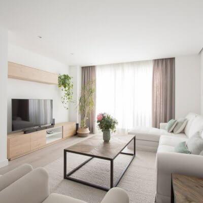 El mueble de TV de la serie NORWAY combina un mueble bajo de acabado roble y estantes blancos, con un módulo en altura, perfecto para ganar almacenaje extra. La gran alfombra lisa en tono beige es otro de los grandes protagonistas.
