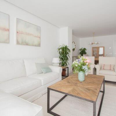 En la zona de estar, los protagonistas son los tonos neutros de los tapizados y textiles El sofá blanco desenfundable y las butacas gemelas tienen tapizados diferentes pero líneas redondeadas muy similares. Todo el mobiliario es de R de Room.