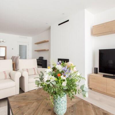 En la estancia, de casi 30 m2, diferenciamos claramente la zona de estar de la de comedor. Jugamos con los tonos neutros y las maderas para crear un ambiente cálido y muy acogedor. Todo el mobiliario es de R de Room.