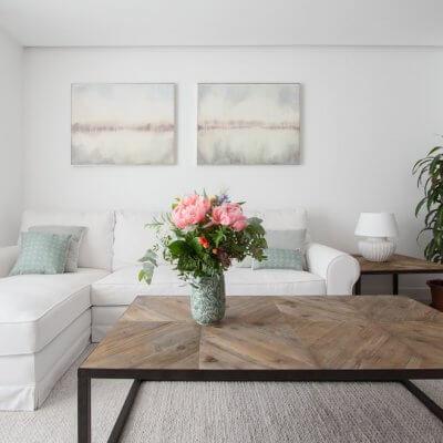 En la zona de estar, las plantas y dos mesas gemelas de madera y hierro lacado en negro dan el toque cálido. El sofá blanco es desenfundable. Todo el mobiliario es de R de Room.