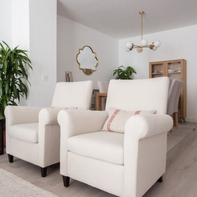 En la zona de estar, los protagonistas son los tonos neutros de los tapizados y textiles. Las butacas gemelas separan el estar del comedor y permiten disfrutar del espacio de chimenea. Todo el mobiliario es de R de Room.