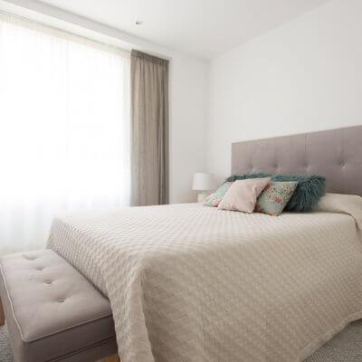 Diseñamos el dormitorio principal en tonos neutros. El cabecero de capitoné y el banco de pie de cama, ambos tapizados en tela gris de efecto aterciopelado, son los grandes protagonistas.
