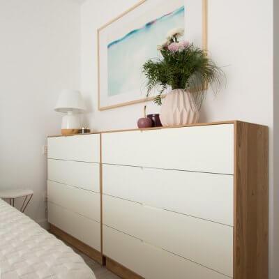 Dos cómodas de fondo reducido en chapado de roble y lacado blanco aumentan la capacidad de almacenamiento del dormitorio sin comprometer los pasos hacia la cama. Por sus dimensiones (96 x 98 x 40 cm), encajan en el hueco como un guante.