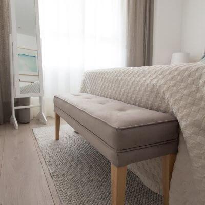 El banco de pie de cama tapizado en gris (a juego con el cabecero) sirve como descalzadora y para dejar los cojines por la noche. El espejo con puerta es perfecto para tener todos los complementos ordenados.
