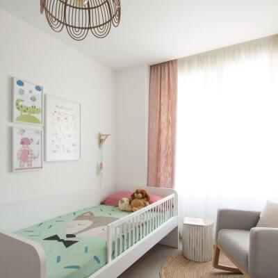 La decoración se plantea en tonos neutros (como la cama nido blanca o la mecedera gris), con toques naturales (en la alfombra de yute y la lámpara de bambú), y una combinación de dos colores, verde y rosa, en los textiles.