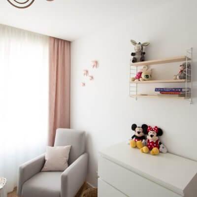 El espacio de lectura o lactancia está formado por una mecedora tapizada gris, una alfombra de yute y una estantería STRING POCKET.