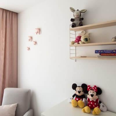 Una estantería String Pcket y un conjunto de 4 golondrinas de cerámica esmaltada en color rosa decoran la pared de este dormitorio infantil.