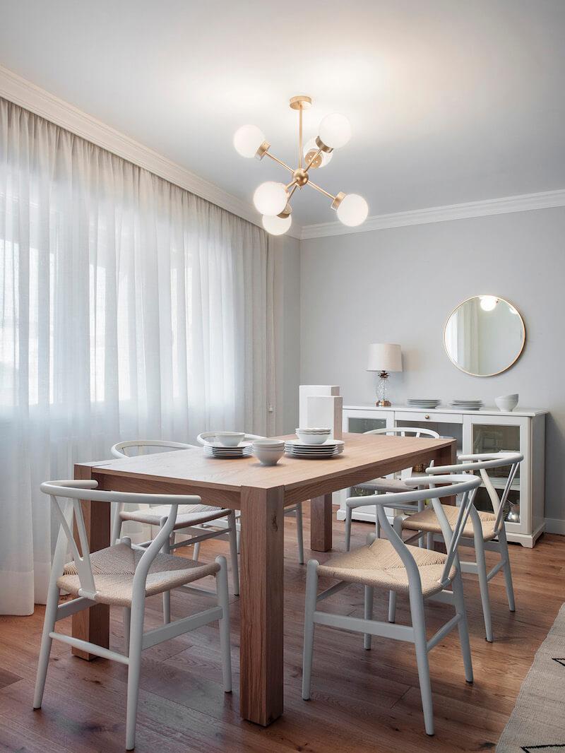 Comedor de vivienda en Madrid. Mesa rectangular de madera de roble extensible. Sillas CH24 blancas. Lámpara suspendida dorada. Comedor contemporáneo, luminoso y acogedor. Proyecto de reforma e interiorismo de R de Room.