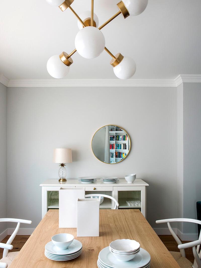 Comedor de vivienda en Madrid. Mesa rectangular de madera de roble extensible. Sillas CH24 blancas. Lámpara suspendida dorada. Comedor contemporáneo, luminoso y acogedor.