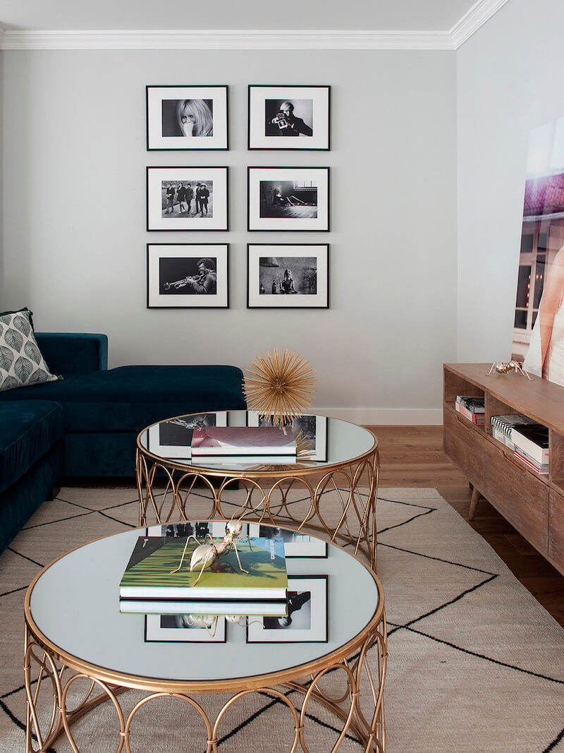 Salón de vivienda en Madrid. Sofá de terciopelo verde. Mesas de centro doradas. Alfombra tipo Beni Ouarain de fondo blanco y rombos negros. Collage de fotografías en blanco y negro.