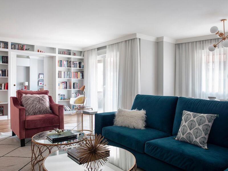Salón de vivienda en Madrid. Zona de estar con sofá de terciopelo verde y butaca de terciopelo rosa. Librería a medida con puerta corredera doble integrada. Mesas de centro doradas. Proyecto de reforma e interiorismo de R de Room.