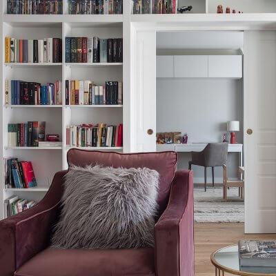 Salón de vivienda en Madrid. Zona de estar con butaca de terciopelo rosa. Librería a medida con puerta corredera doble integrada. Mesas auxiliares doradas. Proyecto de reforma e interiorismo de R de Room.